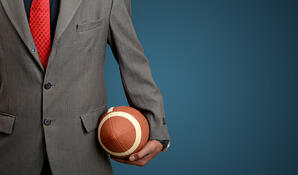 Professional Suited Man with american football ball on blue banner background.