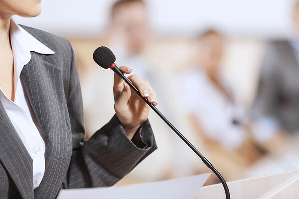 Businesswoman standing on stage and reporting for audience-1