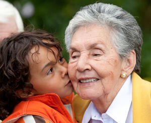 Grandson giving a kiss to his grandmother