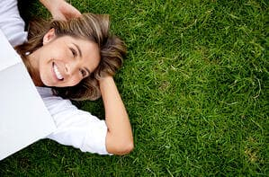 Woman relaxing outdoors looking happy and smiling